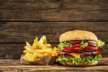 gourmet burger: Delicious hamburger with french fries on wooden table Stock Photo