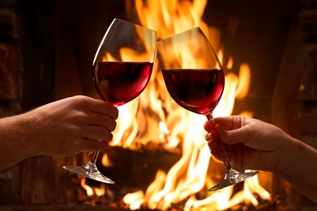 Hands toasting wine glasses in front of lit fireplace Stockfoto