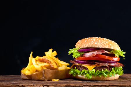 Deliziosi hamburger con patatine fritte sul tavolo in legno Archivio Fotografico - 54094191