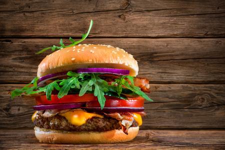 pasteleria francesa: Deliciosa hamburguesa con patatas fritas en la mesa de madera