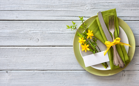 party table: Spring table place setting with daffodils. Holidays background