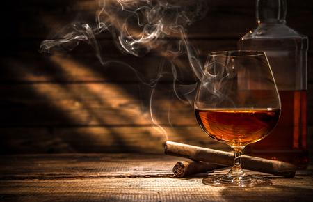 botella de whisky: Vaso de whisky con el consumo de cigarros y cubitos de hielo sobre la mesa de madera
