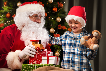 obtain: Santa Claus and a little boy. Boy holding gifts in front of Christmas Tree Stock Photo