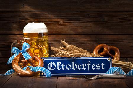 comida alemana: pretzels bávaras originales con jarra de cerveza en la tabla de madera. fondo de Oktoberfest