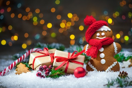 snow man party: Gingerbread man with Christmas presents in snow Stock Photo