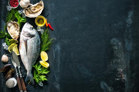 Heerlijke verse vis en oesters met aromatische kruiden, specerijen en groenten op donkere leisteen plaat Stockfoto