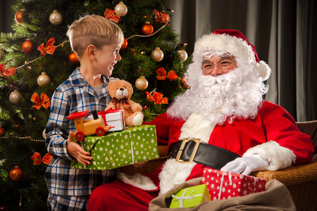 Santa Claus and a little boy. Boy holding gifts in front of Christmas Tree photo