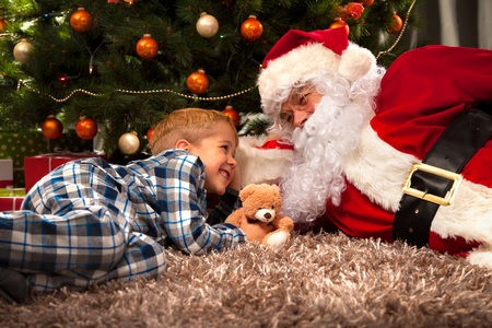 Santa Claus and a little boy in conversation in front of Christmas Tree photo