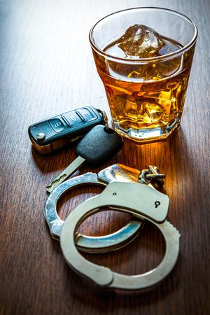 Whisky con las llaves del coche y el concepto de las esposas para beber y conducir