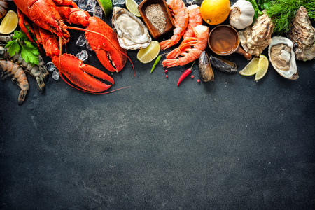 Shellfish plate of crustacean seafood with fresh lobster, mussels, oysters as an ocean gourmet dinner background Standard-Bild