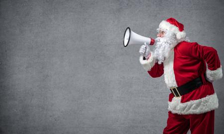 Santa Claus shouting using megaphone over gray background Stock Photo