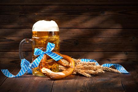 木の板にビール ジョッキを持つ元バイエルン プレッツェル。オクトーバーフェストの背景 写真素材