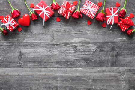 Valentijnsdag vintage achtergrond met rode rozen en geschenkdozen op een houten bord