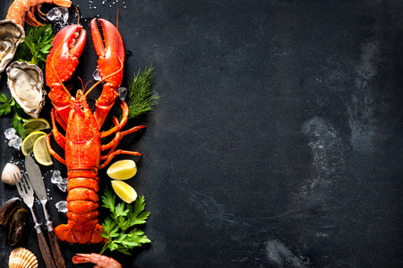Shellfish plate of crustacean seafood with fresh lobster, mussels, shrimps, oysters as an ocean gourmet dinner background 스톡 콘텐츠