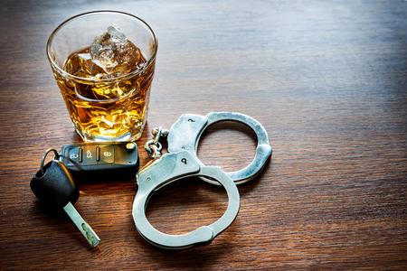 Whiskey avec les clés de voiture et le concept des menottes pour l'alcool au volant Banque d'images