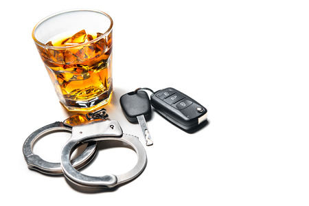 under the influence: Whiskey with car keys and handcuffs concept for drinking and driving Stock Photo