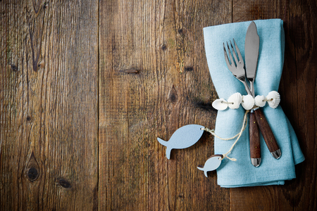 shell fish: Fish cutlery tied with empty fish shaped tag on wooden table with copy space. Menu card for restaurants Stock Photo