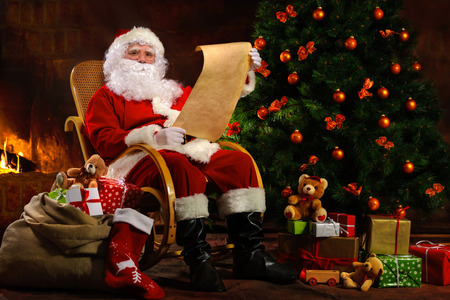 christmas toy: Santa Claus sitting in front of fireplace near Christmas tree with a bag full of presents and a wish list Stock Photo