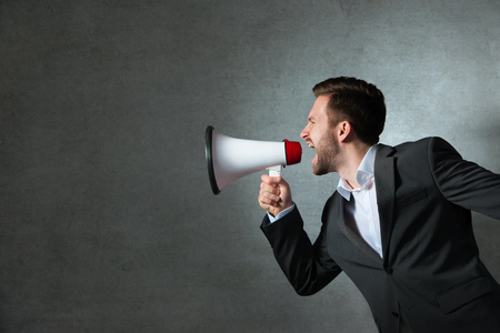 Young handsome shouting man using megaphone over grey background photo