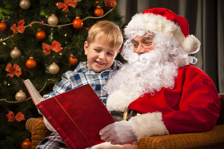 Santa Claus and a little boy reading together a book or list in front of Christmas Tree photo
