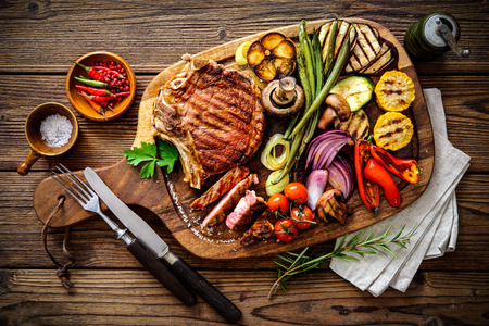 Beef steak with grilled vegetables and seasoning on serving board block Stok Fotoğraf