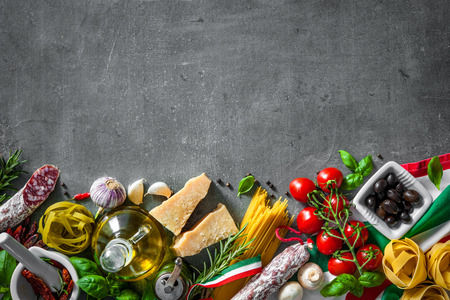 ingredientes de la comida italiana en el fondo de la pizarra