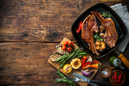 griddle: Roasted lamb meat with vegetables on grill pan on wooden background Stock Photo
