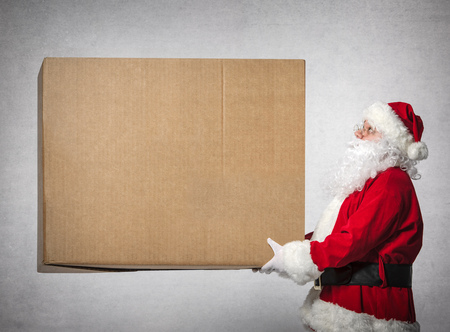 generous: Santa Claus holds a big gift box with copyspace for your text