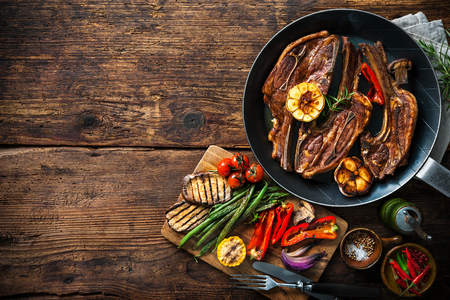 lamb: Roasted lamb meat with vegetables on grill pan on wooden background Stock Photo