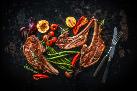 cook griddle: Roasted lamb meat with vegetables on dark background Stock Photo