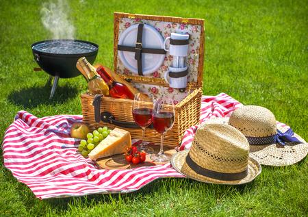 Picknick-Einstellung mit Rotweingläsern, Picknickkorb Korb und brennende Feuer in einem tragbaren Grill