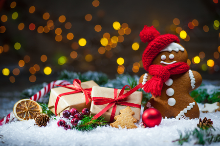 gingerbread man: Gingerbread man with Christmas presents in snow Stock Photo