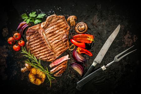 griddle: Beef T-Bone steak with grilled vegetables and seasoning on dark background