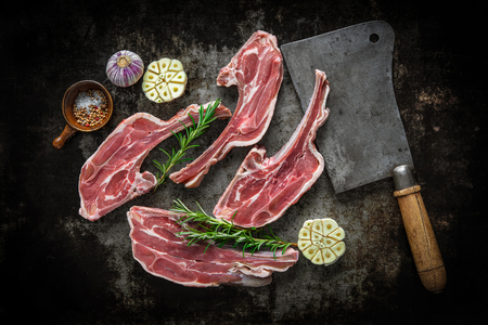 dark meat: Raw fresh lamb meat and meat cleaver on dark background
