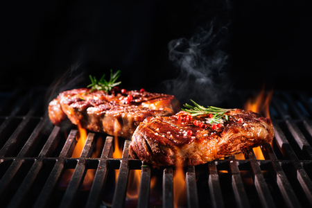 barbecue: Beef steaks on the grill with flames