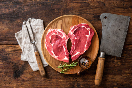 Heart shape raw fresh veal meat steaks with rosemary, pepper and salt on wooden background