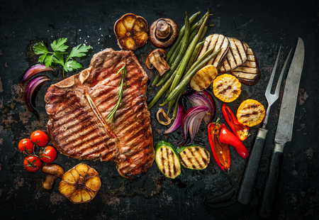 cook griddle: Beef T-Bone steak with grilled vegetables and seasoning on dark background