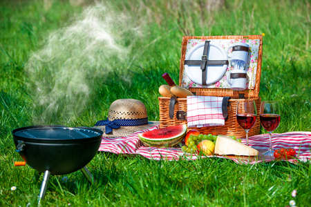 picknick: Picnic setting with red wine glasses, picnic hamper basket and burning fire in a portable barbecue