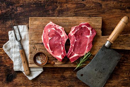 carne cruda: la forma del corazón crudos frescos filetes de carne de ternera con romero, pimienta y sal en el fondo de madera