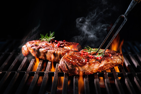 Rindersteaks auf dem Grill mit Flammen Lizenzfreie Bilder