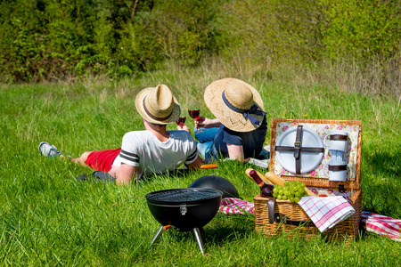 Picnic setting with red wine glasses, picnic hamper basket and burning fire in a portable barbecue photo