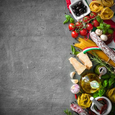 Ingredientes de la comida italiana en el fondo de la pizarra Foto de archivo - 56267594