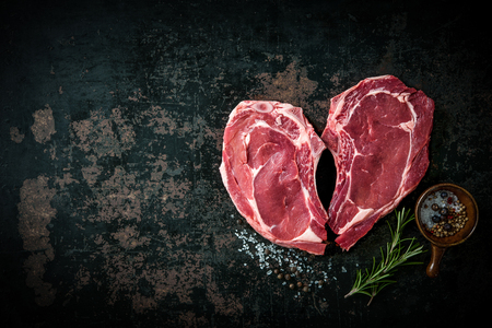 dark meat: Heart shape raw fresh veal meat steaks with rosemary, pepper and salt on dark background