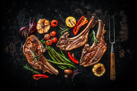 comidas: carne de cordero asado con verduras en el fondo oscuro