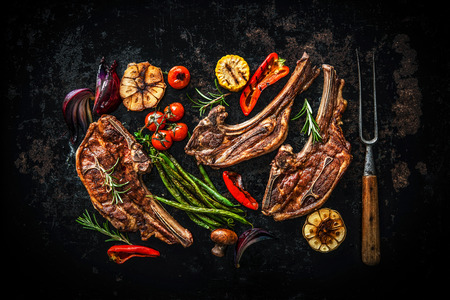 cooked: Roasted lamb meat with vegetables on dark background Stock Photo