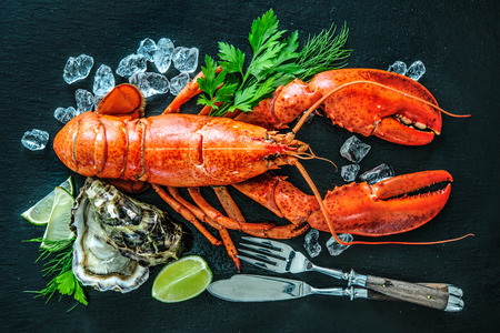 black stone: Shellfish plate of crustacean seafood with fresh lobster, mussels, oysters as an ocean gourmet dinner background Stock Photo