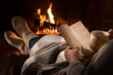 home keeping: Woman resting with cup of hot drink and book near fireplace
