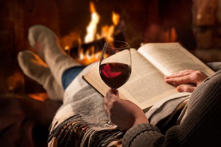 Vrouw die met een glas rode wijn en boeken in de buurt van open haard