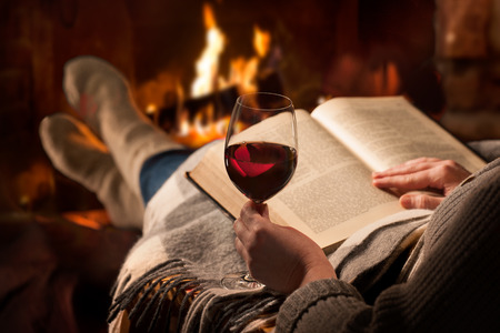 Woman resting with glass of red wine and book near fireplace Zdjęcie Seryjne - 56702272