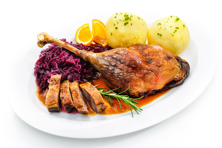 menue: Crusty goose leg with braised red cabbage and dumplings isolated on white